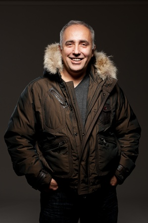mid life: portrait of laughing middle aged man in winter coat over dark background