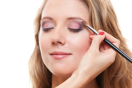 esthetician: portrait of lovely young woman having make up over white background
