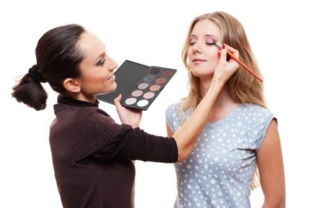esthetician: professional make-up artist applying eye shadow. isolated on white background