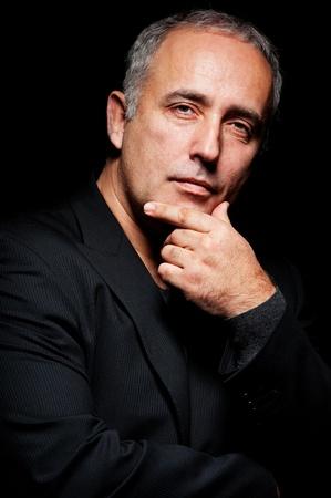 portrait of pensive senior man over black background