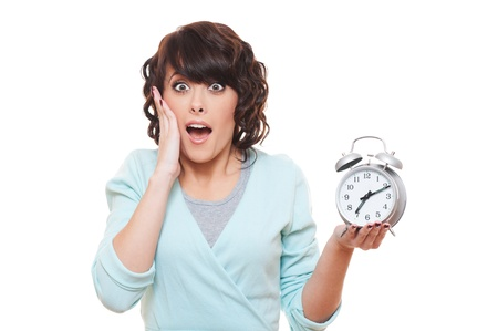 startled: portrait of shocked woman with alarm clock over white background