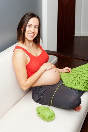smiley pregnant woman sitting on sofa and crocheting  photo