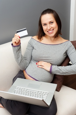 smiley young pregnant woman sitting on sofa with laptop and credit card  photo