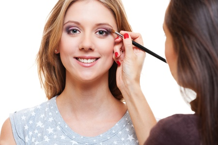 smiley blonde having visage by make-up artist. over white background photo