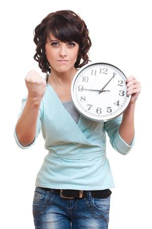 punctual: mujer joven sosteniendo una estricta reloj y haciendo gestos amenazantes. aisladas sobre fondo blanco