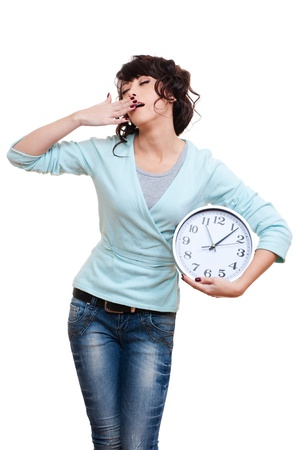 slumberous: tired woman holding clock and yawning. isolated on white background  Stock Photo