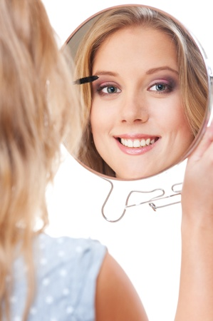 smiley woman applying mascara and looking in hand mirror over white background photo
