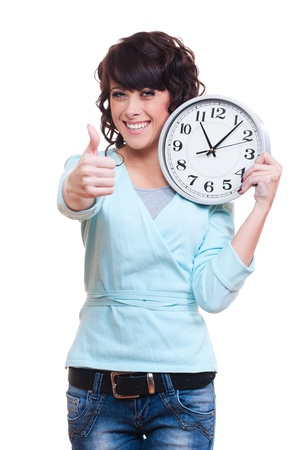 punctual: smiley young woman holding clock and showing thumbs up. isolated on white background  Stock Photo