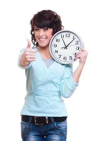 punctual: sonriente mujer joven que sostiene el reloj y que muestran los pulgares para arriba. aisladas sobre fondo blanco Foto de archivo