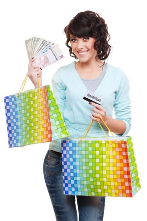 smiley young woman holding paper money, plastic card and shopping bags. isolated on white background  photo