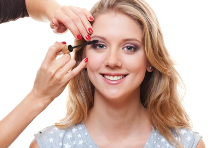 portrait of young pretty woman applying mascara over white background  photo