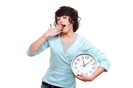 slumberous: young woman holding clock and yawning. isolated on white background  Stock Photo