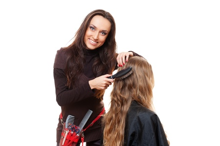 smiley hairdresser doing hairstyle. isolated on white background  photo