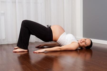 pregnancy yoga: portrait of healthy smiley pregnant woman doing exercise at home