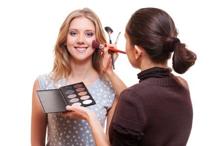 mujer maquillandose: maquillaje profesional artista que trabaja con el modelo. estudio de fotografía en blanco