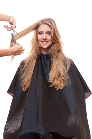 hairdresser cutting hair of smiley woman