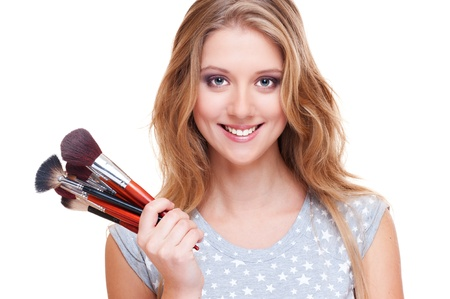 bright picture of smiley woman with make-up brushes over white photo
