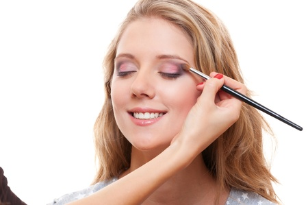 studio shot of lovely young woman having make up over white background photo