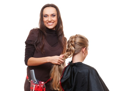 studio shot of smiley hairdresser doing a plait. white background  photo