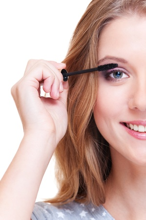 close up portrait of smiley woman doing make up. white background photo