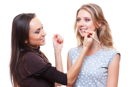 studio picture of make up artist applying lipstick to the model. white background photo
