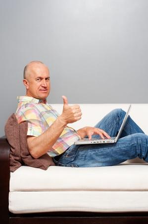 senior ordinateur: homme senior avec un ordinateur portable � la maison montrant thumbs up
