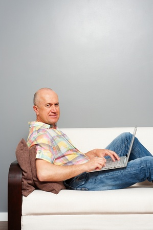 senior man at home with notebook. looking at camera photo