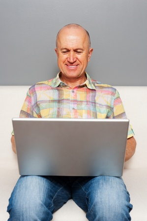 smiley senior man sitting with laptop at home photo