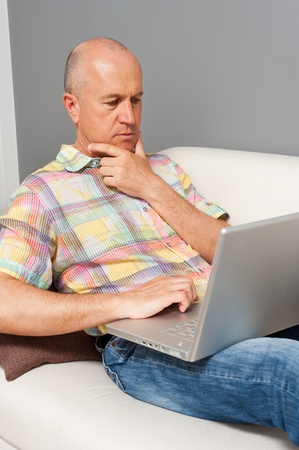 serious senior man with laptop at home photo