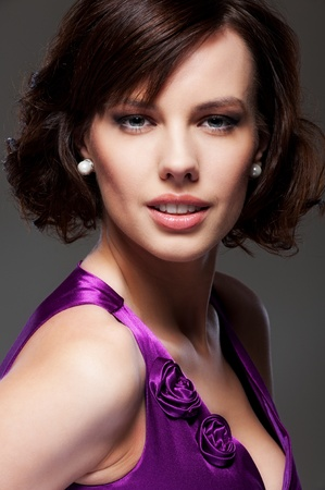 studio portrait of beautiful smiley brunette over dark background photo