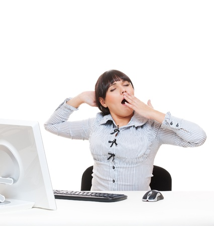 studio shot of tired businesswoman yawning on her workplace. isolated on white photo