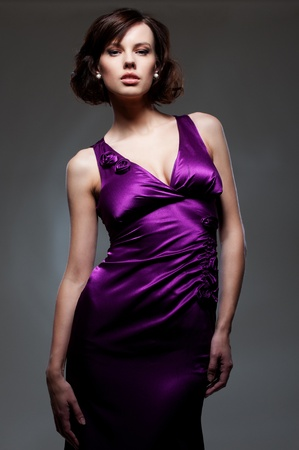 young model in violet dress over dark background photo