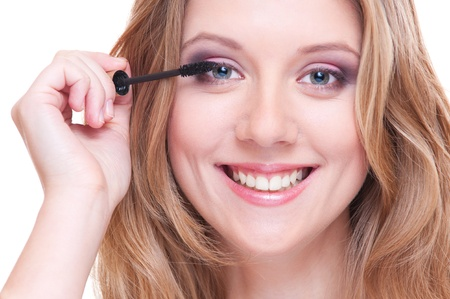 closeup portrait of young woman applying make up. white background photo