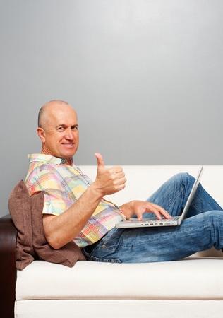 daumen hoch: �ltere Smiley Mann mit Notebook zeigt Daumen nach oben