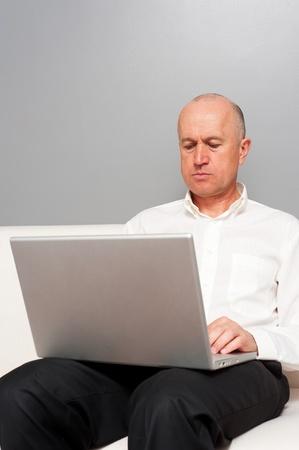 senior man in white shirt with laptop photo