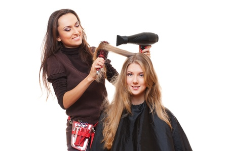hairdryer: studio shot of hairdresser and young woman. isolated on white