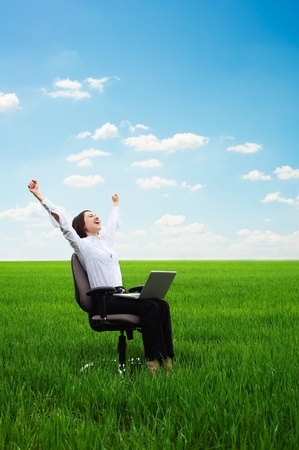 bright picture of happy young woman with laptop on the meadow photo