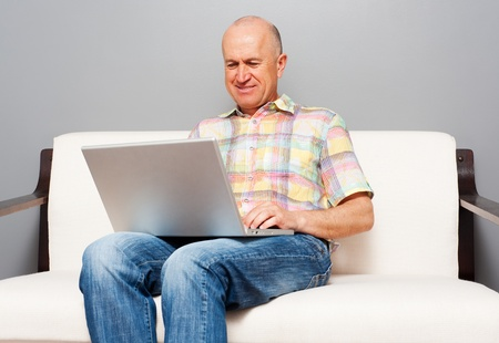 smiley senior man using laptop at home photo