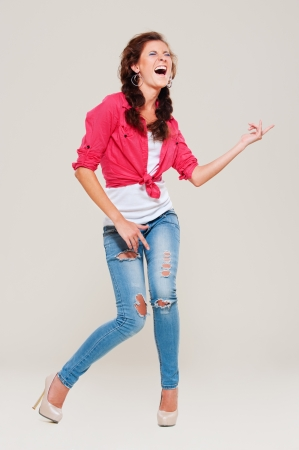 studio shot of happy woman playing air guitar over grey background photo
