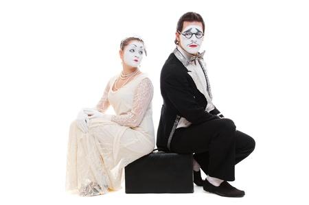 pantomima: foto de estudio de dos mimos que se sienta en la maleta aislado en blanco Foto de archivo