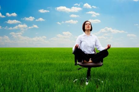 mujer meditando: Empresaria practicar yoga en la pradera en día soleado Foto de archivo