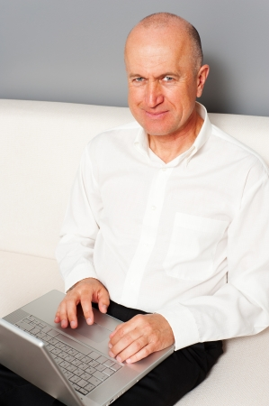 smiley senior man searching something in internet photo