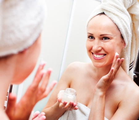 smiley woman looking in mirror and applying cream  photo