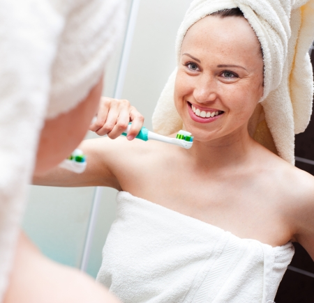 smiley woman with toothbrush looking at mirror photo