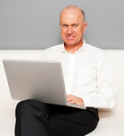 senior man with laptop online at home photo