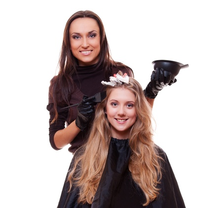 studio shot of hairdresser dyeing woman's hair. isolated on white photo