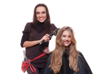 smiley hairdresser doing curly hair. isolated on white background photo