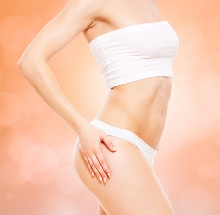 beautiful healthy womans body in white underwear over blurred background photo