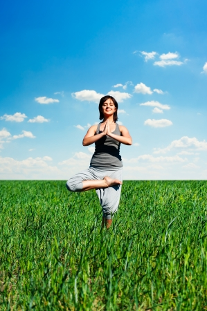 happy young woman practicing yoga at the field  photo