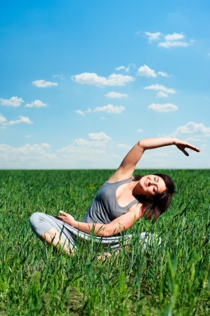 young woman doing yoga exercises at the field at sunny day photo